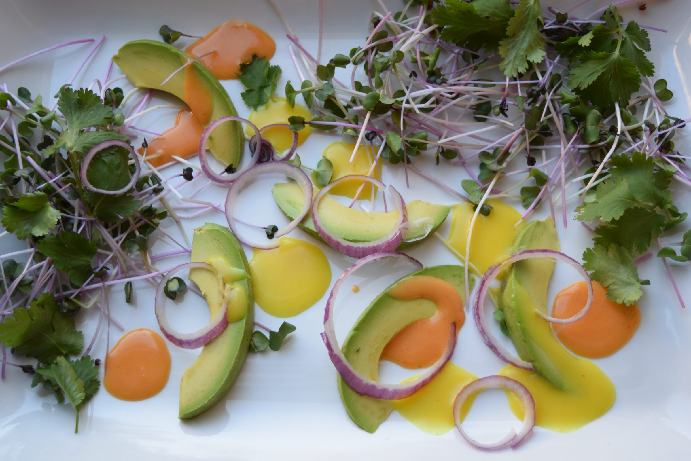 Avocados, sprouts, and orange sriracha salad dressing